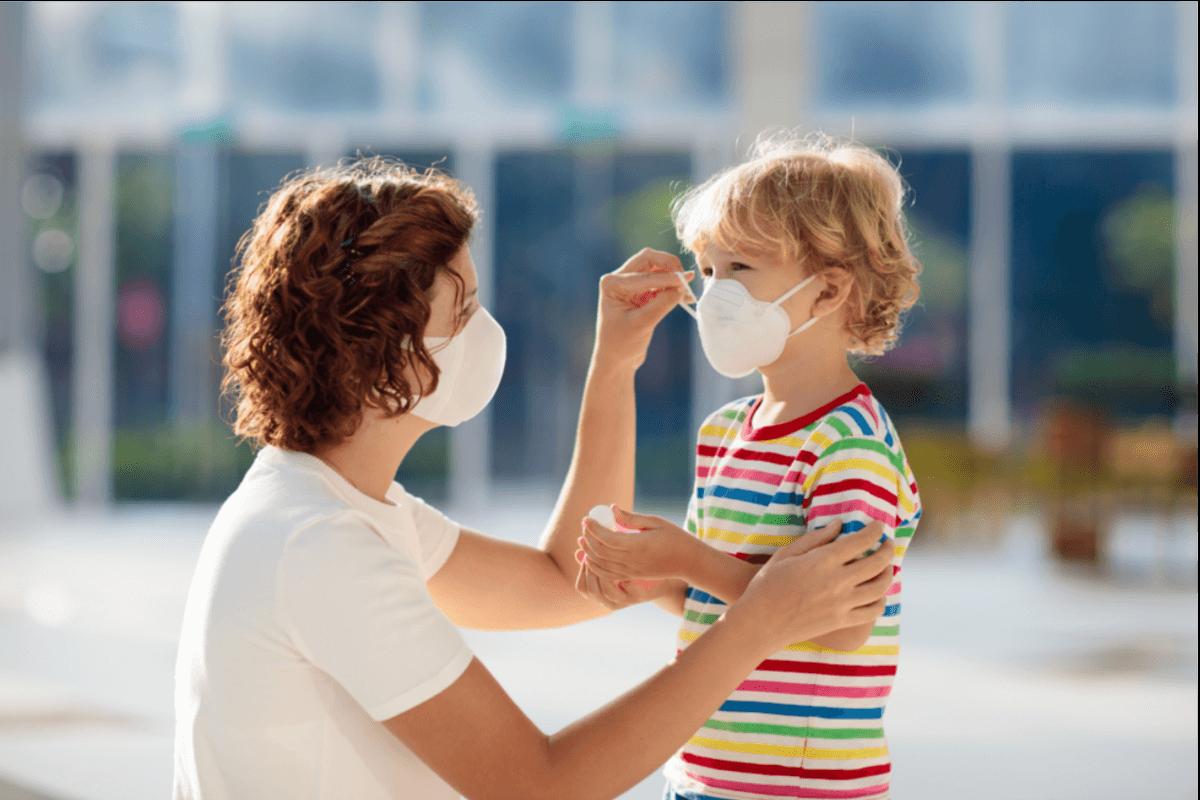 Beim Anlegen einer Mund-Nasen-Maske benötigen Kinder häufig Hilfe.